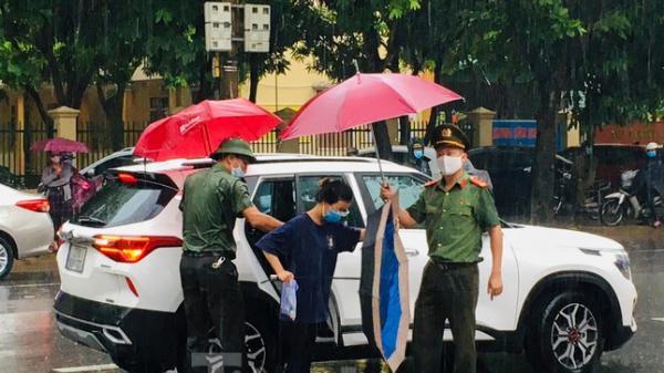 Hình ảnh đẹp chiến sĩ công an dầm mưa che chắn cho sĩ tử